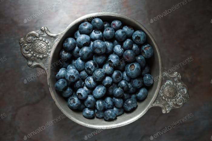 Berry bilberry in a tin bowl on a gray slate closeup