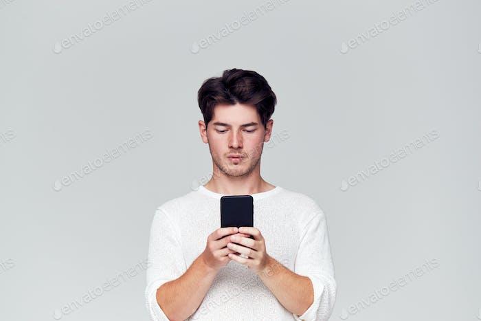Studio Schuss von kausally gekleidet jungen Mann mit Handy
