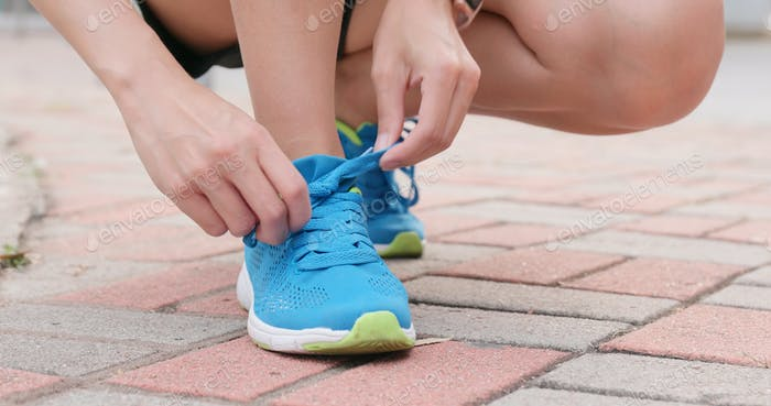 Sport woman fixing shoes lace
