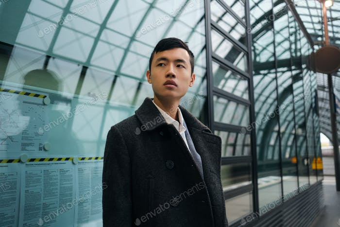 Young stylish Asian businessman in coat intently looking away waiting train at subway station