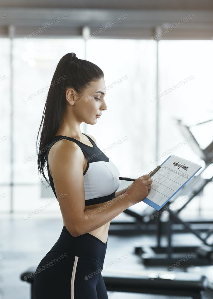 Personal trainer with clipboard building workout schedule for client in gym