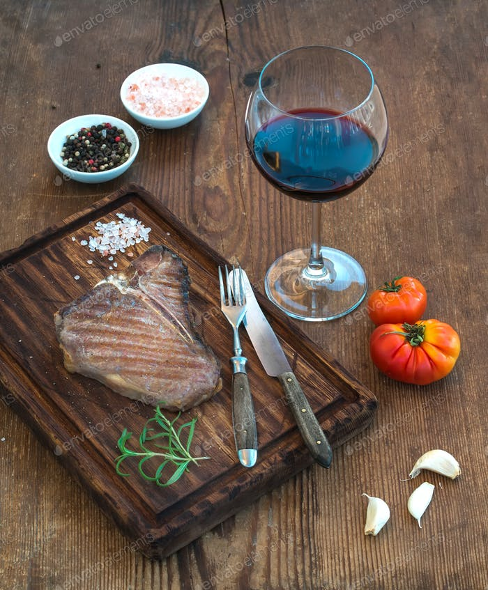 Cooked meat t-bone steak on serving board with garlic cloves, tomatoes, rosemary