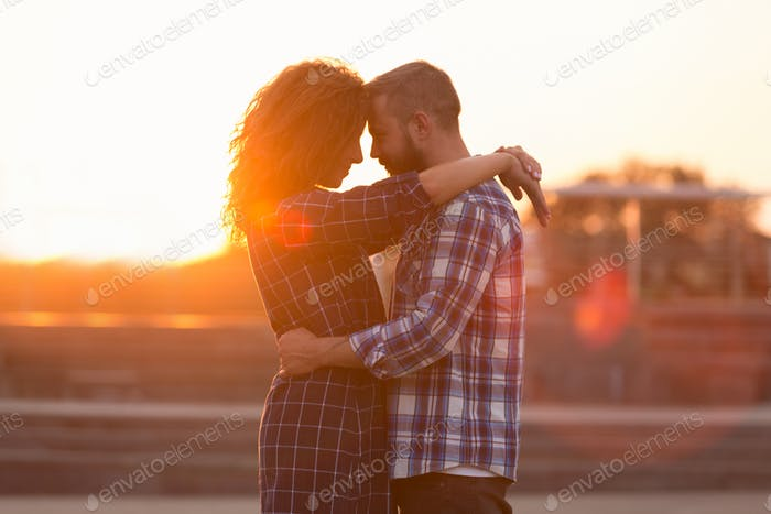 Beloved couple embracing and touching their foreheads at sunset