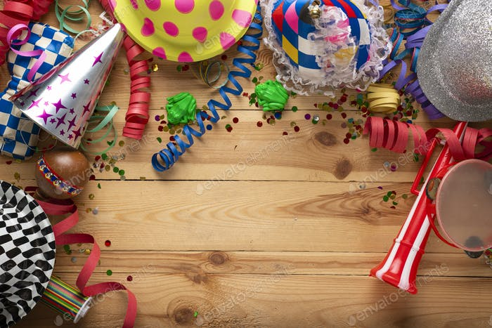 Carnival background on a wooden surface. Masks, hats, coiled streamers, confetti and many more