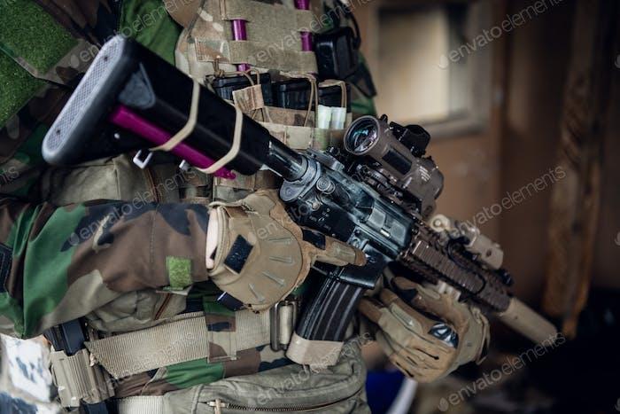 Waffen close-up auf einen militärischen Mann im Inneren des Gebäudes stehen und warten auf Befehl
