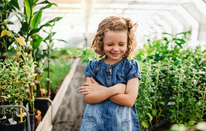 Portrait of small girl standing in the greenhouse, grimacing