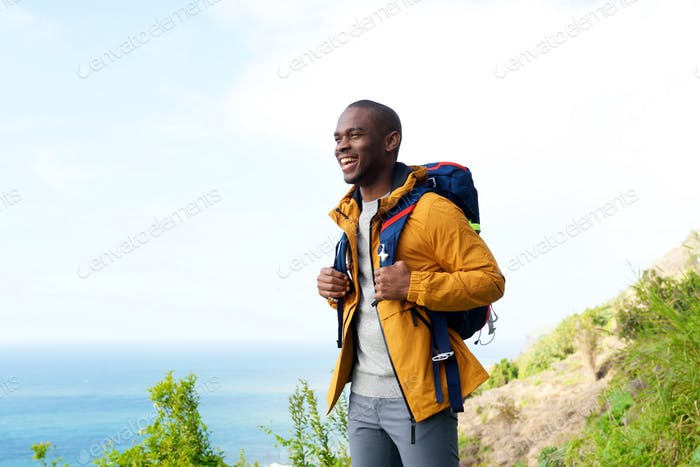 happy african american man with backpack outdoors