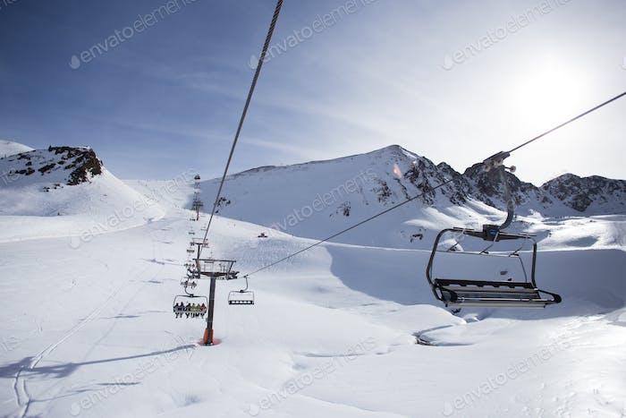 Mountain ski lift over slopes on sunny day