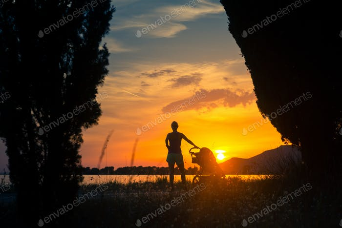 Mother with baby in stroller enjoying motherhood at sunset