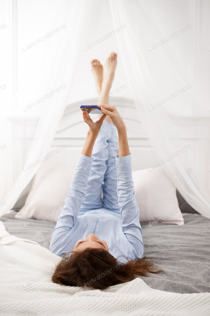 Brunette girl in the light-blue pajama lays with her legs up on the canopy bed on the gray sheet
