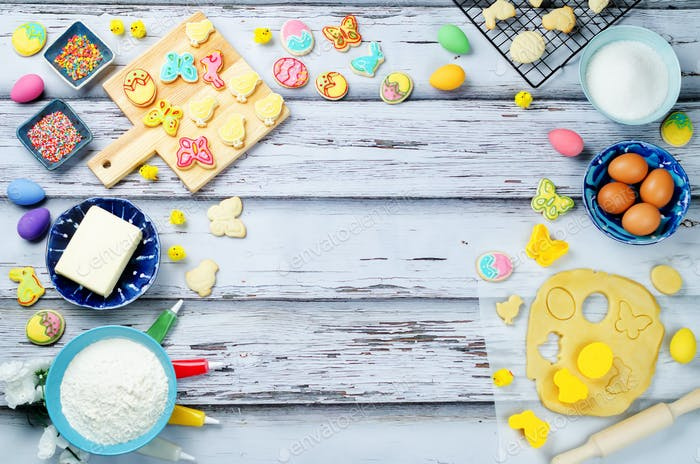 Wood background with Sugar Easter cookies and ingredients for ba