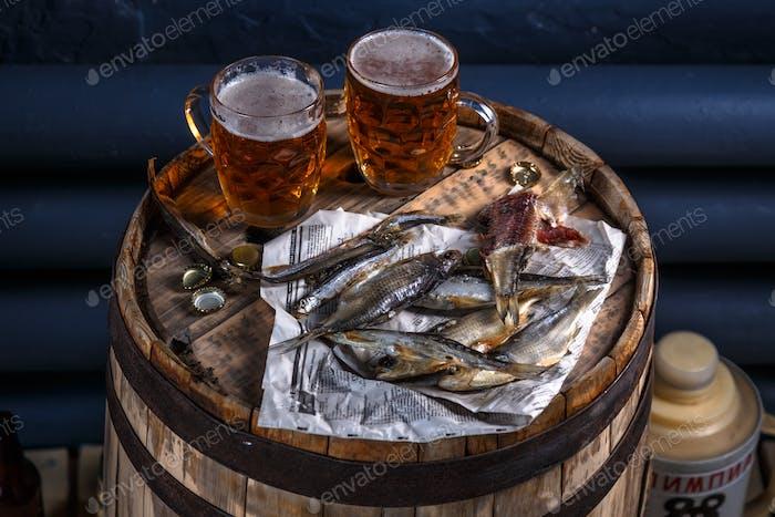 Bierbecher mit getrockneten Fischen auf einem Holzfass