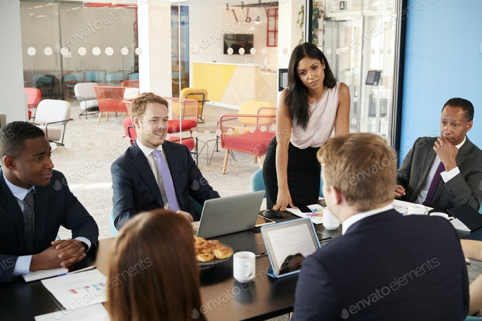 Female boss stands listening to colleagues at team meeting