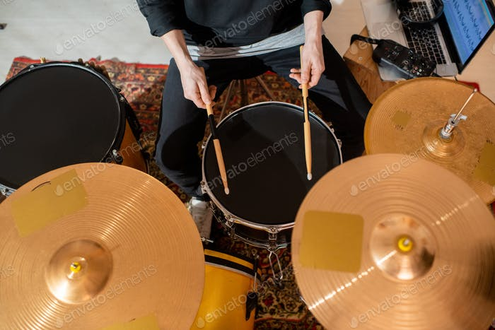 Overview of hands of young drummer or musician with drumsticks having rehearsal