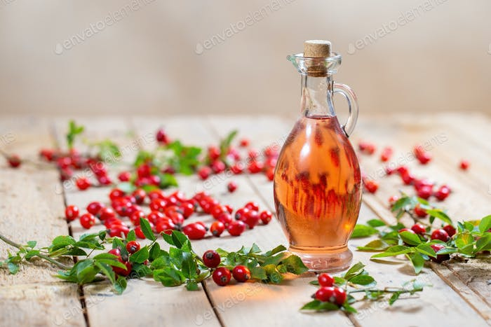 Bottle of rosehip oil on wooden palette with berries around
