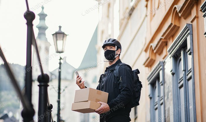 Delivery man courier with face mask and smartphone delivering in town