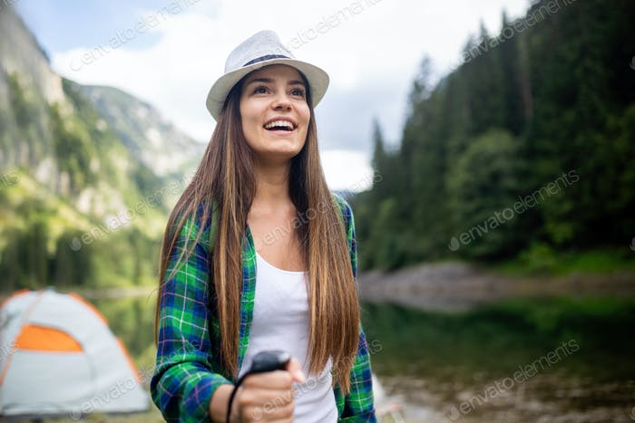 Young woman traveling with backpack hiking in mountains