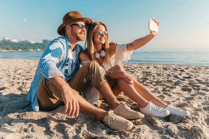 young attractive smiling happy man and woman in sunglasses lying on sand beach