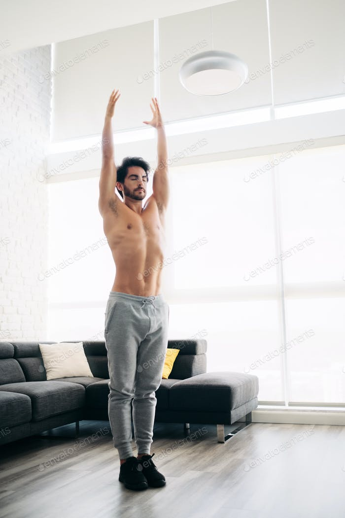 Man Practicing Yoga At Home Doing Sun Salutation Routine