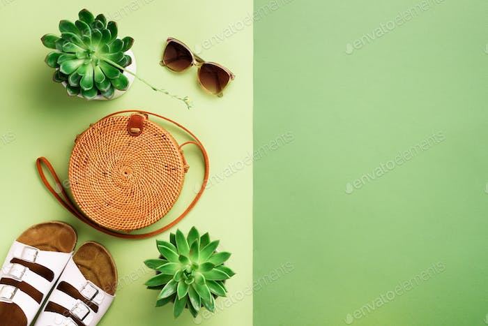 Stylish rattan bag, birkenstocks, succulent, sunglasses on green background. Banner. Top view with