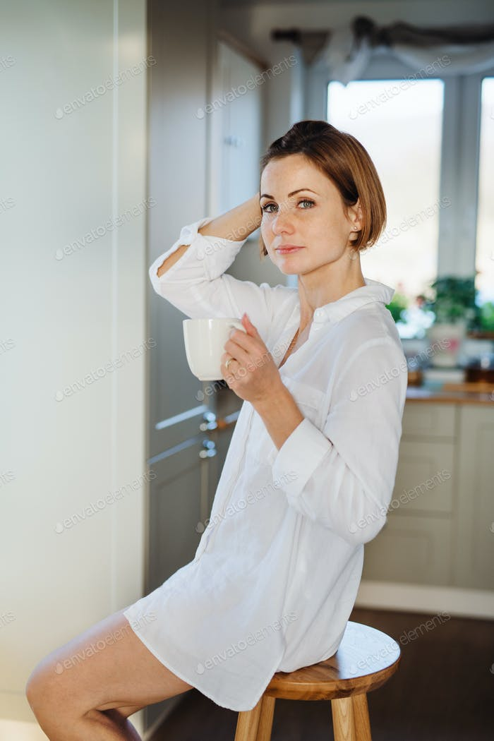 A young woman with cup of coffee sitting on a stool indoors, holding cup of coffee.