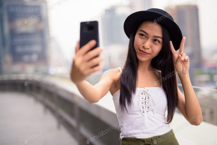 Young beautiful Asian tourist woman taking selfie against view of the city