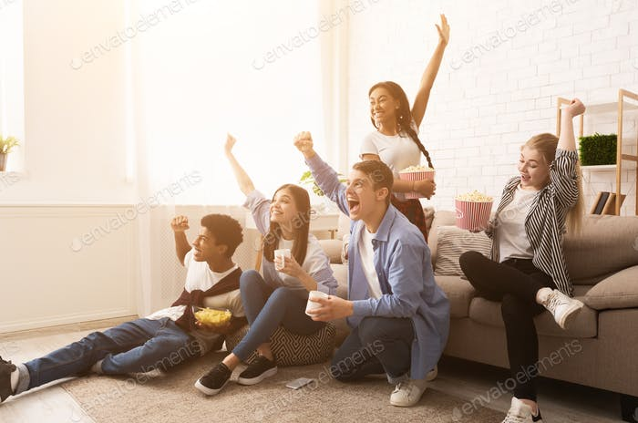 Teen football fans cheering for favourite team