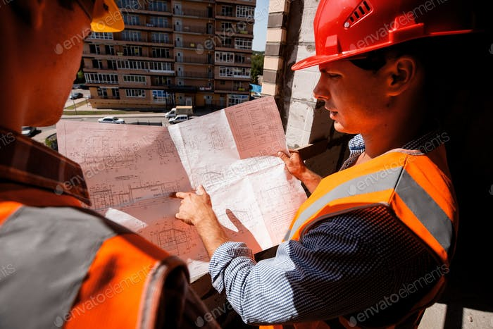 Architect and structural engineer dressed in shirts, orange work vests and helmets explore