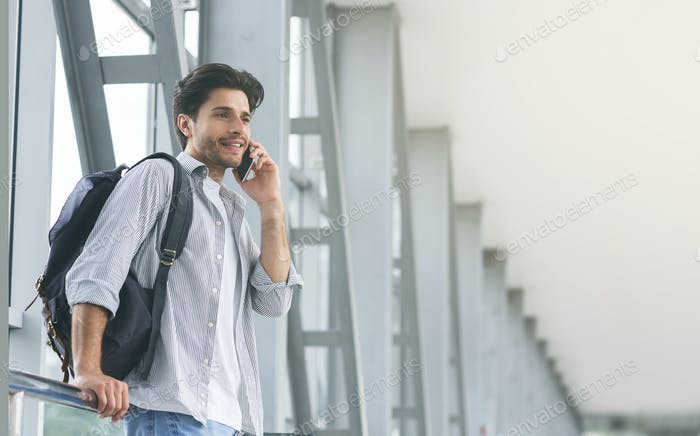 Young man traveller talking on mobile phone in airport