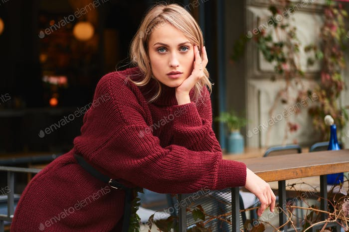 Beautiful blond girl in knitted sweater confidently looking in camera outdoor