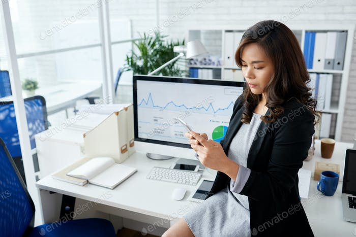 Serious Businesswoman Reading Text Messages