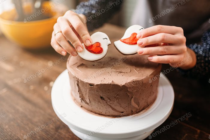 Female hands decorate cake with cookies