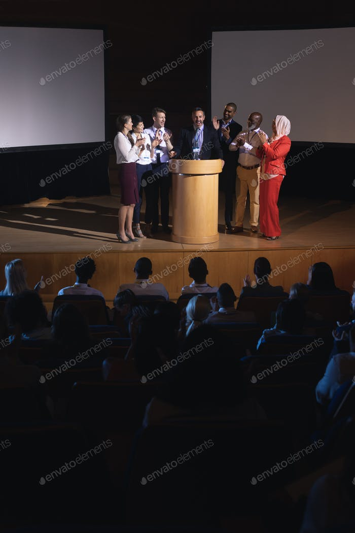 Diverse business colleagues clapping hand for there colleague in the auditorium stage
