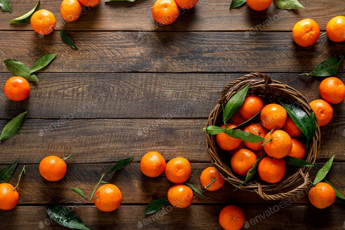 Tangerines, fresh mandarin oranges, clementines with leaves on wooden background