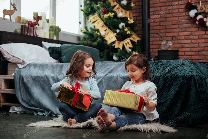 Christmas holidays with gifts for these two kids that sitting indoors