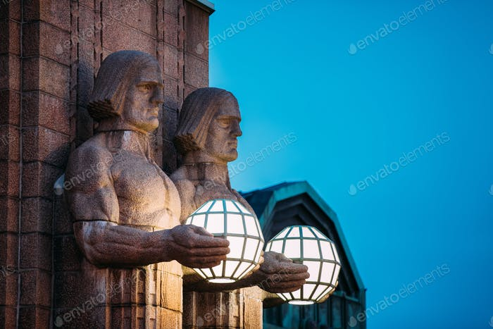 Helsinki, Finland. Night View Of Two Pairs Of Statues Holding Th