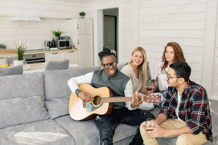 Happy African guy singing by guitar while sitting on couch among his friends