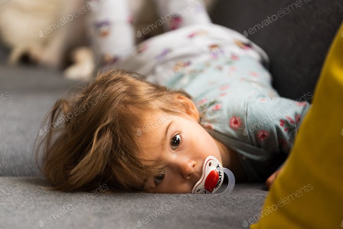 Cute 2 year old Baby girl on a bed on her belly with head on sofa. Bright interior