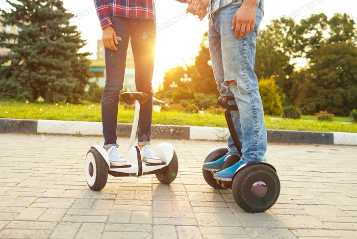 Young couple riding hoverboard