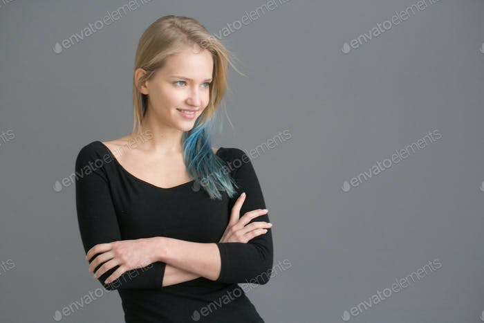 Woman color hair with blue colored hairstyle ower gray wall