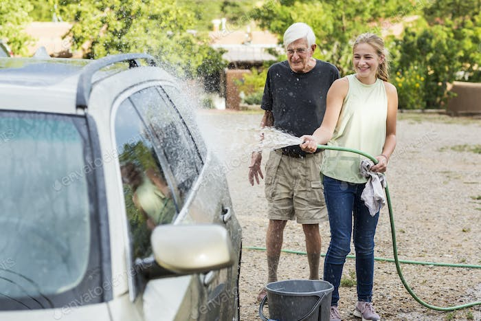senior grandfather and his 13 year old grand daughter washing a car together in driveway