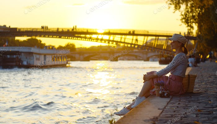 Young girl by the river at sunset in Paris