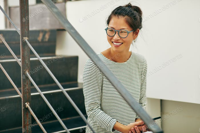 Laughing Asian businesswoman sitting on office stairs reading text messages