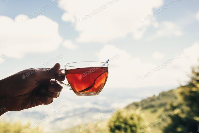 Glas heißen Tee auf Holztisch bei Fensterlicht