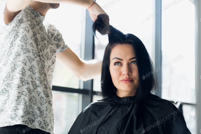 Unrecognizable hairdresser creating hairstyle for beautiful brunette woman