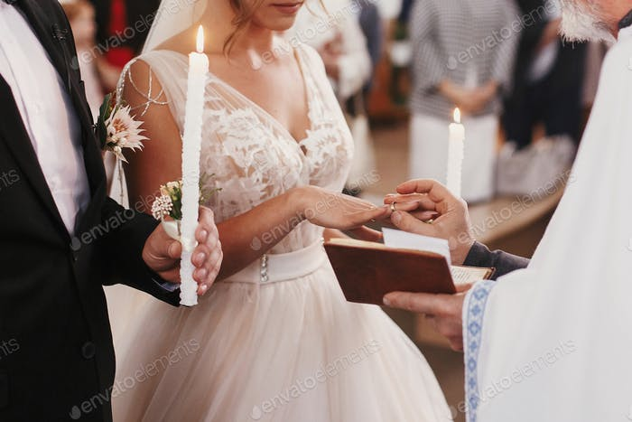 Priester setzen auf goldenen Ehering auf Braut Finger
