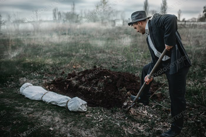 Killer is digging a grave for the victim in forest