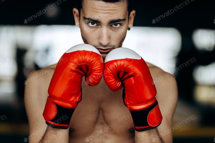 Sportsman with a naked torso keeps his hands in the red boxing gloves next to his face in the boxing