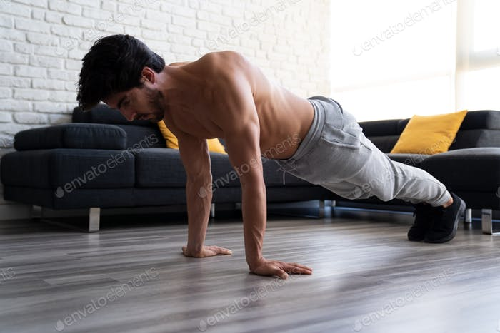 Young adult male working out at home doing push ups.