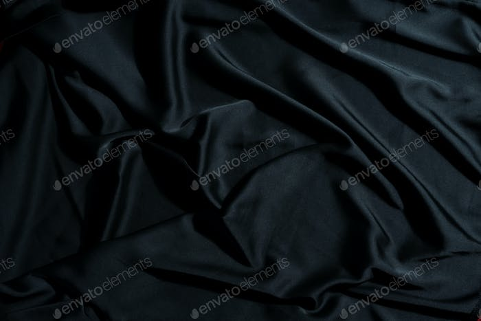 Crumpled textile fabric background of black color